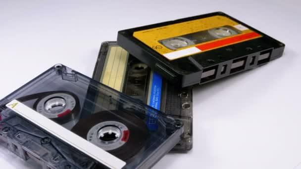 Tři Vintage Audio kazety otáčet na bílém pozadí