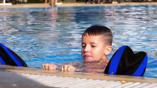 Happy Boy with Flippers Swims in a Pool with Blue Water. Slow Motion