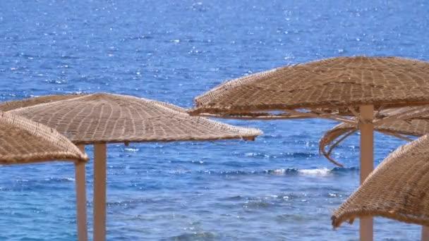 Deštníky na pozadí moře na prázdné pláži v Egyptě