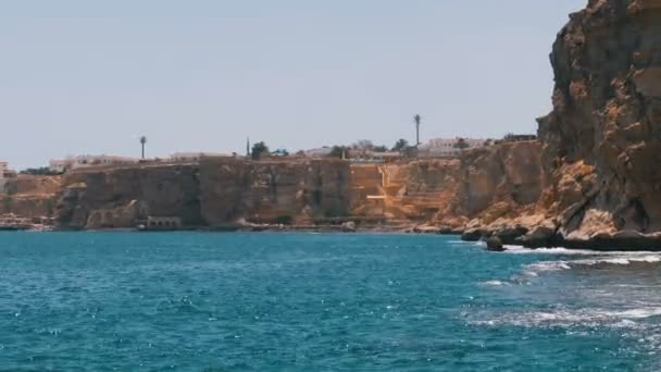Rocky Beach in Egypt. Beach in a bay on the coastline with waves in the blue sea and coral reefs