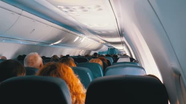 Cestující uvnitř kabiny osobních letadel sedícího na židlích během letu