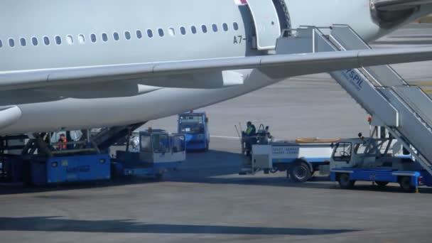 Pohled na dráhu letiště s letadly a podpůrnými pracovníky