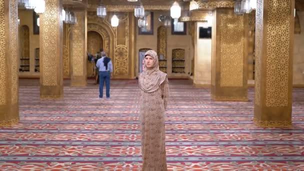 Žena oblečená v jeptišky v plášti stojí uvnitř islámského chrámu. Egypt