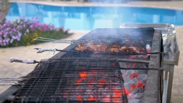 Csirke barbecue főznek egy nagy grill egy szakács a Hotel a medence kék víz. Egyiptom