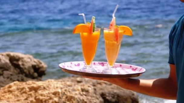 exotische Cocktails in einem Glas mit einem Strohhalm auf einem Tablett auf dem Hintergrund des Meeres. Ägypten.
