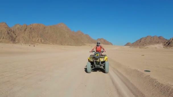 Szexi lány a lovaglás quad Bike az egyiptomi sivatagban. Mozgás dinamikus nézete.