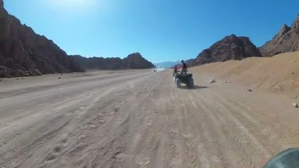 Szexi nő lovaglás a quad Bike az egyiptomi sivatagban. Mozgás dinamikus nézete.