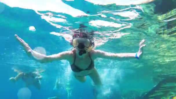junge Frau mit Schnorchelmaske und Schlauch schwimmt im roten Meer in der Nähe von Korallenriffen