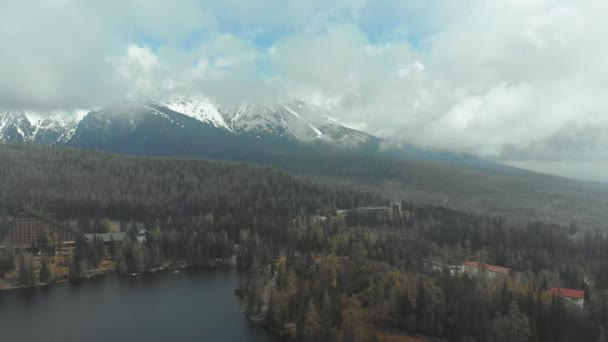 Letecký pohled na Strbske Pleso v oblacích a zasněžených horách. Slovensko