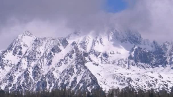 Zasněžený vrchol hory v oblacích. Strbske Pleso. Slovensko. Vysoké Tatry