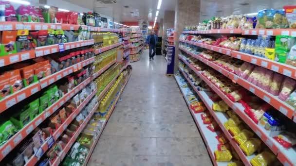 Police se zbožím v supermarketu. Nákupy v potravinách. Procházka obchodem s potravinami.