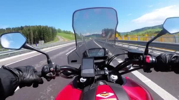 Motorcyklista jízda na prázdné dálnici. Výhled zpoza kola motorky. Pov