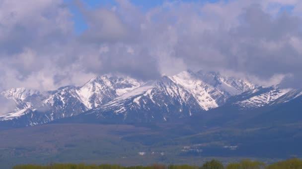 Panoramatický výhled na zasněžené Vysoké Tatry. Horské vrcholy v oblacích