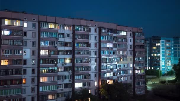 Multistorey épület változó ablakvilágítással éjszaka. Időintervallum