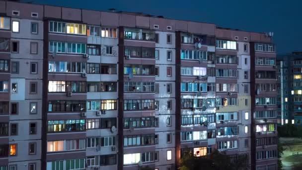 Geschossiges Gebäude mit nachts wechselnder Fensterbeleuchtung. Zeitraffer