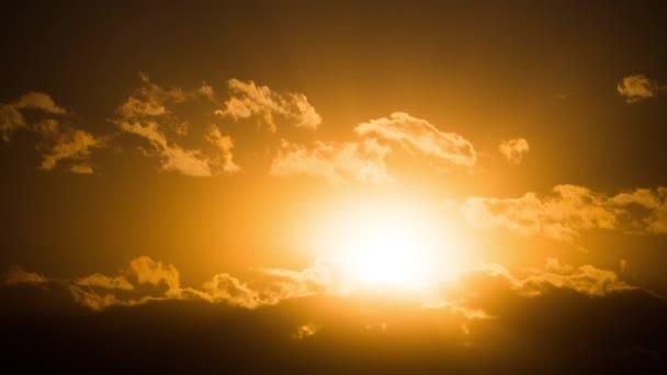 Dramatický západ slunce nad mraky. Timelapse. Velké žluté slunce se pohybuje přes obzor.