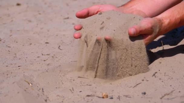 Písek padá z mužské ruky na pláž v pomalém pohybu. Špinavý písek v rukou mužů