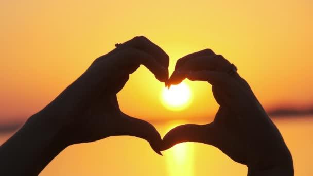 Silueta ženských rukou držících se za nápis ve tvaru srdce při oranžovém západu slunce