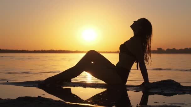 Silhouette of Hot Woman in Swimsuit Lying and Posing on Evening Beach at Sunset