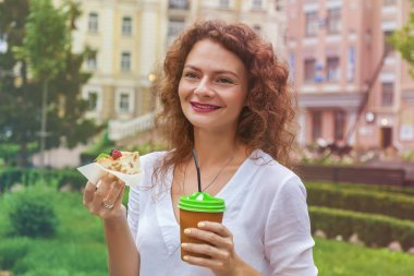 A beautiful girl in the park drinks a coffee cup from a paper cup through a straw and holds a delicious apple pie.the girl drinks coffee through straws
