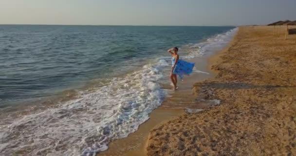 schöne junge Mädchen am Strand am Meer in einem blauen Kleid. das Mädchen am Strand in einem Kleid am Meer.