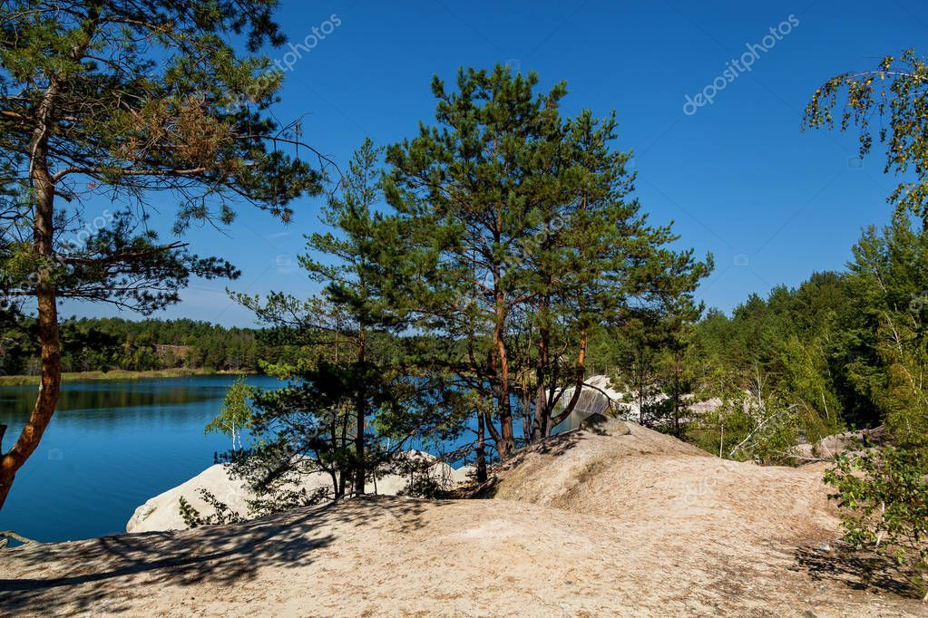 Korostyshevsky quarry flooded granite quarry on the outskirts of the city of Korostyshev in the Zhytomyr region, a tourist attraction. Labradorite, gabbro and gray granite were mined here. Landscape of a blue lake with clear water surrounded by fores
