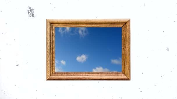Konceptuální kreativní časová prodleva videa modré oblohy s rychle se pohybujícími kumulativními mraky v dřevěném rámu proti bílé zimní obloze s pomalu padajícím sněhem. Myšlenka na světlou budoucnost, naději, víru.