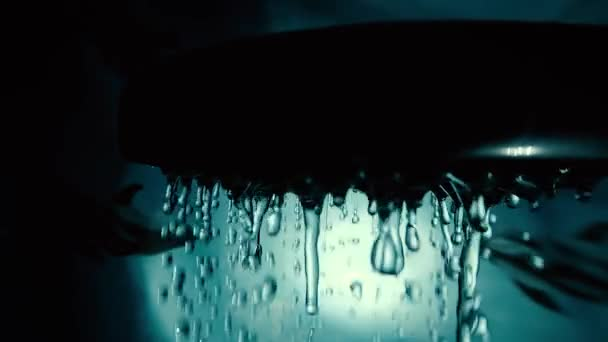 Extrém lassított felvételű makró videó, amin vízcseppek ömlenek a fürdőszobába egy zuhanyfejről. Közelkép zuhanyzó vízcseppekkel.