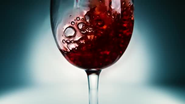 Creative macro slow motion video of red wine pouring into a glass. Glass with pouring red wine close-up. Old retro grunge vintage style.