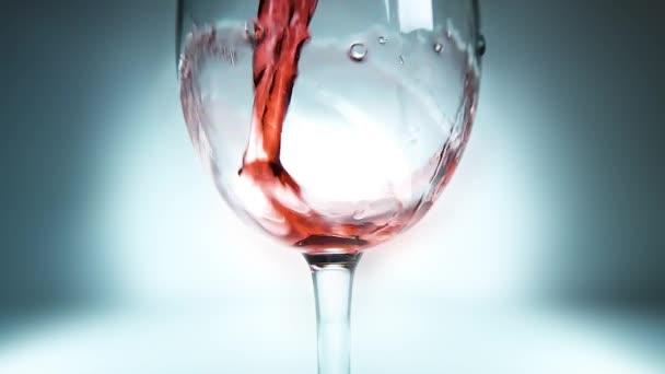 Tvůrčí makro zpomalené video červeného vína nalévajícího se do sklenice. Sklenice s nalitím červeného vína zblízka.