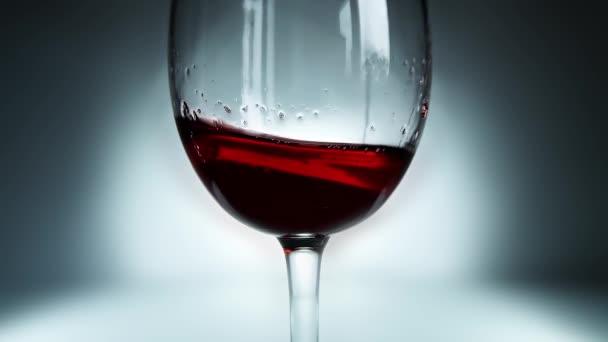 Kreatives Makro-Zeitlupenvideo von Rotwein, der wie Wellen in einem Glas von Seite zu Seite spritzt. Glas mit spritzendem Wein in Großaufnahme. Alter Retro Grunge Vintage Stil.