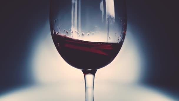 Tvůrčí makro zpomalené video červeného vína cákajícího ve sklenici ze strany na stranu jako vlny. Sklenice se stříkajícím vínem zblízka. Starý retro grunge vintage styl s příjemným, mírně měkkým vybledlý.