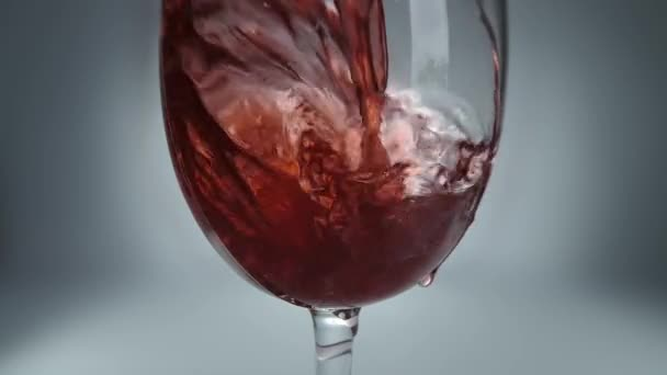 Creative macro slow motion raw video of red wine pouring into a glass. Glass with pouring red wine close-up.