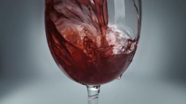 Tvůrčí makro zpomaluje syrové video červeného vína nalévajícího se do sklenice. Sklenice s nalitím červeného vína zblízka.