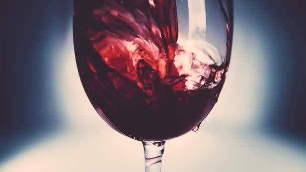 Kreatives Makro-Zeitlupenvideo von Rotwein, der in ein Glas gegossen wird. Glas mit einschenkendem Rotwein in Großaufnahme. Alter Retro Grunge Vintage Stil mit angenehmer, leichter und weicher Verfärbung.