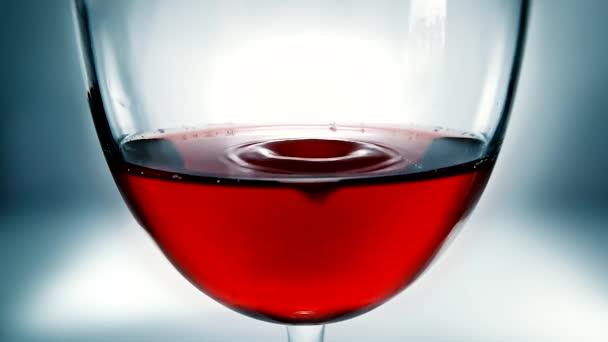 Kreatives Makro-Zeitlupenvideo von Rotwein in einem Glas und einem fallenden Tropfen Wein. Ein Glas mit einem langsam fallenden Tropfen Wein in Nahaufnahme.