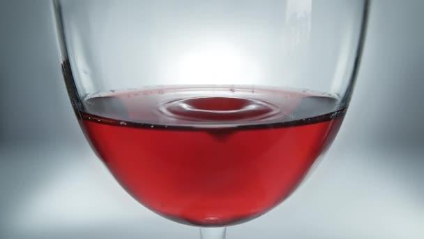 Kreative Makro-Zeitlupe Rohvideo von Rotwein in einem Glas und einem fallenden Tropfen Wein. Ein Glas mit einem langsam fallenden Tropfen Wein in Nahaufnahme.