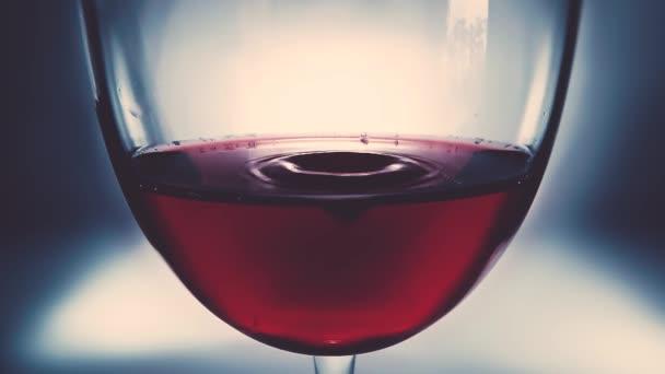 Tvůrčí makro zpomalené video červeného vína ve sklenici a kapky vína. Sklenice s pomalu padajícími kapkami vína zblízka. Starý retro grunge vintage styl s příjemným měkkým vybledlý.