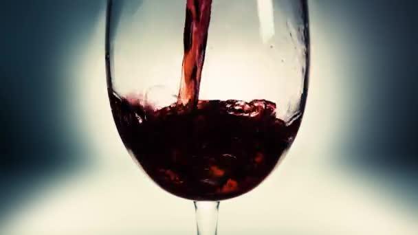Kreatives Makro-Zeitlupenvideo von Rotwein, der in ein Glas gegossen wird. Glas mit einschenkendem Rotwein in Großaufnahme. Alter Retro Grunge Vintage Stil.