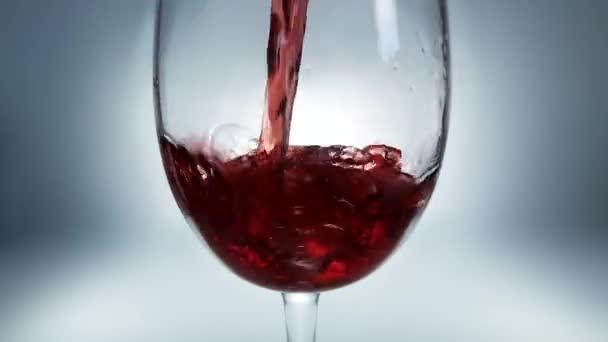 Kreatives Makro-Zeitlupe-Rohvideo von Rotwein, der in ein Glas gegossen wird. Glas mit einschenkendem Rotwein in Nahaufnahme.