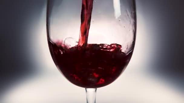 Kreatives Makro-Zeitlupenvideo von Rotwein, der in ein Glas gegossen wird. Glas mit einschenkendem Rotwein in Nahaufnahme.