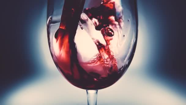 Creative macro slow motion video of red wine pouring into a glass. Glass with pouring red wine close-up. Old retro grunge vintage style with a pleasant, slight and soft faded.