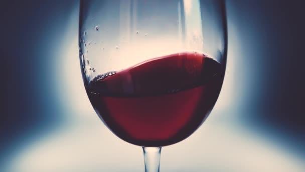 Kreatív makrofilm lassított felvételen vörösbor fröccsenő egy pohár egyik oldalról a másikra, mint a hullámok. Üveg fröccsenő bor közelről. Régi retro grunge vintage stílus egy kellemes, enyhe lágy halvány.