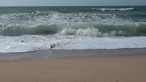 Hullámok törnek be a homokos tengerpartra egy nyugodt délután