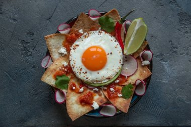 Chilaquiles Mexican tortilla with tomato salsa, chicken and egg close-up on a plate. Horizontal view from above