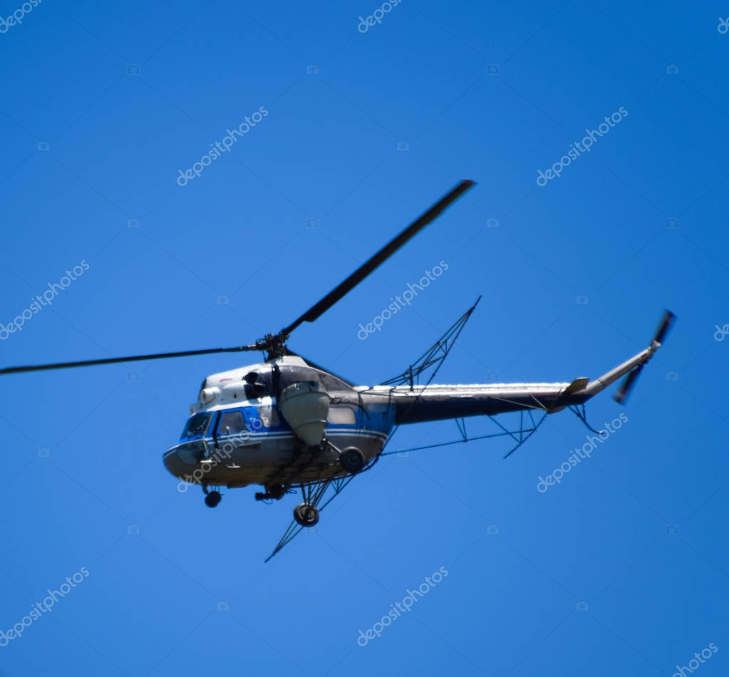 A helicopter of agricultural aviation is flying in the blue sky. Helicopter for spraying fertilizers and pesticides