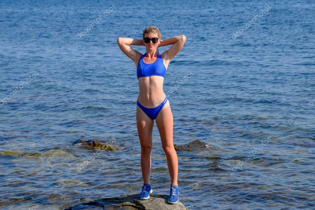 A beautiful girl in a blue bikini walks the pier to the sea. Marine concrete pier. Jumping into the water from the pier. Beautiful Booty Girls