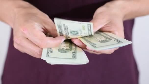 Muž počítá dvacet dolarových bankovek v balíku