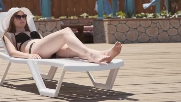 a happy young girl in a black swimsuit and a white hat comes to the lounger and lies down on him. A real rest by the pool. Resort on the sea