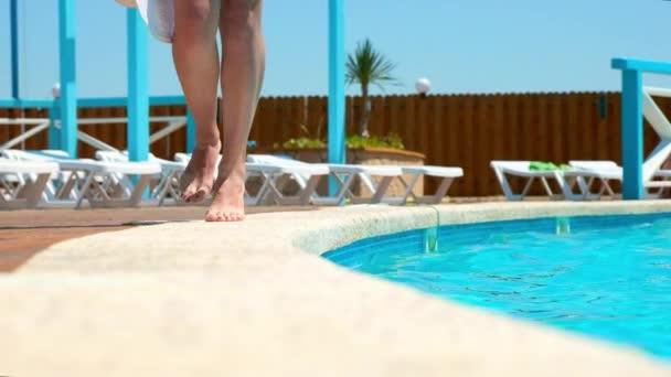 Schöne Frau zu Fuß rund um Pool. Meerblick von Luxusvilla. Beine
